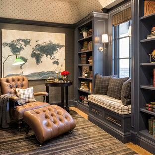ミネアポリスの大きいトラディショナルスタイルのおしゃれなホームオフィス・仕事部屋 (ライブラリー、グレーの壁、淡色無垢フローリング、暖炉なし、自立型机、茶色い床) の写真