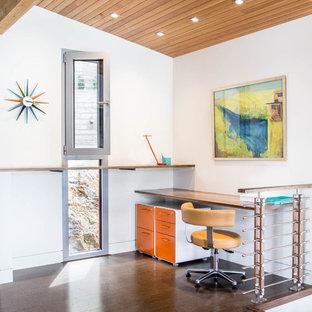 他の地域の小さいミッドセンチュリースタイルのおしゃれな書斎 (白い壁、濃色無垢フローリング、造り付け机、茶色い床) の写真