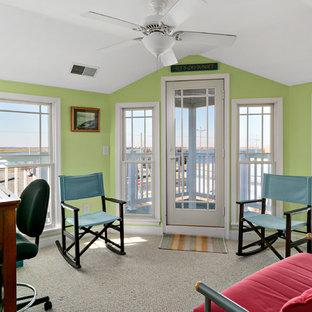 Maritim inredning av ett mellanstort hemmabibliotek, med gröna väggar, heltäckningsmatta, en hängande öppen spis, ett fristående skrivbord och grått golv