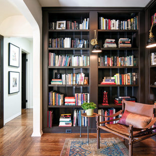 Inspiration for a mid-sized mediterranean medium tone wood floor and orange floor home office library remodel in Los Angeles with black walls