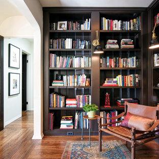 Medelhavsstil inredning av ett mellanstort arbetsrum, med ett bibliotek, svarta väggar, mellanmörkt trägolv och orange golv