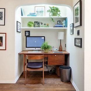 ロサンゼルスの中くらいの地中海スタイルのおしゃれな書斎 (ベージュの壁、無垢フローリング、造り付け机、茶色い床) の写真