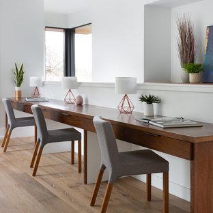 Idéer för att renovera ett funkis hemmabibliotek, med vita väggar, ljust trägolv, ett inbyggt skrivbord och beiget golv