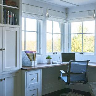 Inredning av ett maritimt mellanstort hemmabibliotek, med vita väggar, mörkt trägolv, en dubbelsidig öppen spis, en spiselkrans i sten, ett inbyggt skrivbord och brunt golv