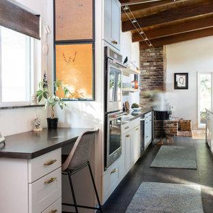Esempio di un ufficio classico di medie dimensioni con pavimento in ardesia, pavimento nero, pareti bianche, scrivania incassata e soffitto in legno