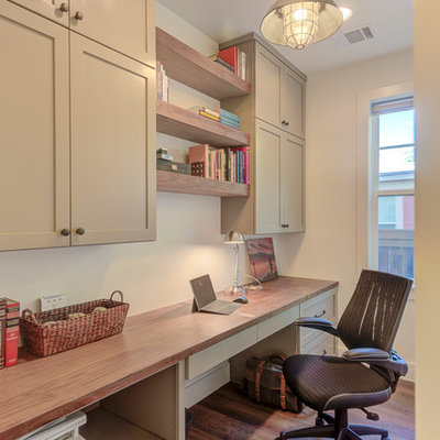 Home office - mid-sized cottage built-in desk dark wood floor and brown floor home office idea in Austin with white walls