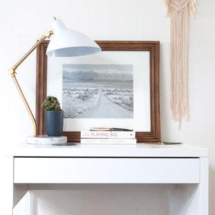 Foto på ett stort minimalistiskt arbetsrum, med vita väggar, heltäckningsmatta, ett fristående skrivbord och svart golv
