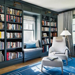 Idee per un grande studio costiero con libreria, pareti gialle, parquet chiaro, scrivania autoportante e pavimento blu