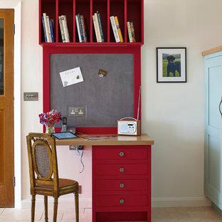 Foto på ett litet lantligt hemmabibliotek, med kalkstensgolv, vita väggar och ett inbyggt skrivbord