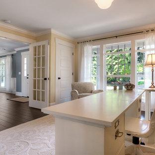 Imagen de despacho clásico, de tamaño medio, sin chimenea, con paredes amarillas, suelo de madera oscura y escritorio independiente