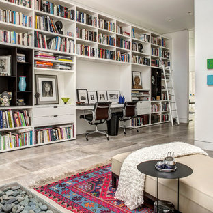 Example of a midcentury modern built-in desk home office library design in Los Angeles with white walls