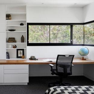 Exempel på ett mellanstort modernt hemmabibliotek, med vita väggar, heltäckningsmatta, ett inbyggt skrivbord och grått golv