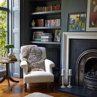 ロンドンのヴィクトリアン調のおしゃれなホームオフィス・書斎 (青い壁、無垢フローリング、標準型暖炉、ライブラリー) の写真