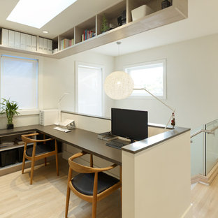 Example of a small trendy built-in desk light wood floor study room design in Vancouver with white walls