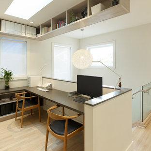 Immagine di un piccolo ufficio design con pareti bianche, parquet chiaro, nessun camino e scrivania incassata