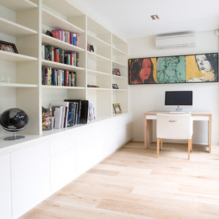 Photo of a contemporary study room in Sydney with white walls, light hardwood floors, a freestanding desk and beige floor.