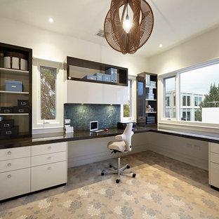 Пример оригинального дизайна: огромное рабочее место в современном стиле с бежевыми стенами, ковровым покрытием, встроенным рабочим столом и разноцветным полом