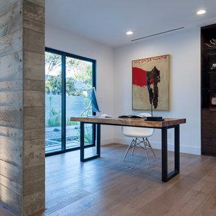 Foto de despacho moderno, de tamaño medio, sin chimenea, con paredes blancas, suelo de madera clara, escritorio independiente y suelo marrón
