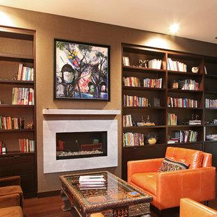 Réalisation d'un grand bureau minimaliste avec un mur gris, un sol en bois foncé, une cheminée ribbon, un manteau de cheminée en pierre et un bureau indépendant.