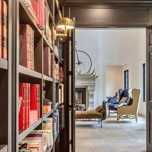 カルガリーの大きいトラディショナルスタイルのおしゃれなホームオフィス・書斎 (ライブラリー、グレーの壁、ライムストーンの床、自立型机、マルチカラーの床) の写真