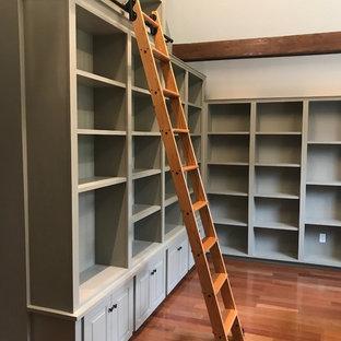 Foto di uno studio stile americano di medie dimensioni con libreria, pareti grigie, pavimento in legno massello medio e pavimento rosso