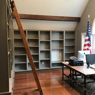 Foto di uno studio american style di medie dimensioni con libreria, pareti grigie, pavimento in legno massello medio e pavimento rosso