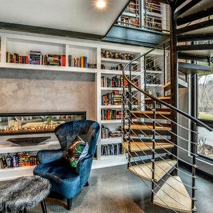 Idee per un grande studio minimal con libreria, pareti beige, pavimento in cemento, camino bifacciale, cornice del camino in cemento, pavimento beige e scrivania autoportante