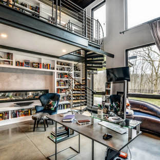 Large contemporary home office and library in Other with a reading nook, beige walls, concrete flooring, a two-sided fireplace, a concrete fireplace surround, a freestanding desk and beige floors.
