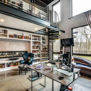 他の地域の大きいコンテンポラリースタイルのおしゃれなホームオフィス・書斎 (ライブラリー、ベージュの壁、コンクリートの床、両方向型暖炉、コンクリートの暖炉まわり、自立型机、ベージュの床) の写真