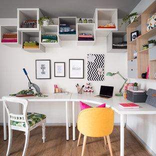 Esempio di un atelier boho chic di medie dimensioni con pareti bianche, pavimento in laminato, nessun camino, scrivania autoportante e pavimento marrone