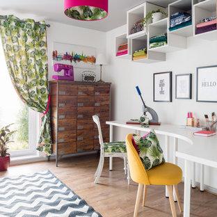 Eklektisk inredning av ett mellanstort hemmastudio, med vita väggar, laminatgolv och ett fristående skrivbord