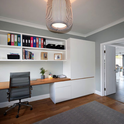 Study room - large contemporary built-in desk medium tone wood floor and brown floor study room idea in London with gray walls