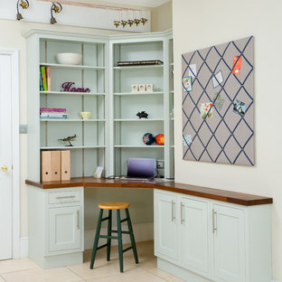 Design ideas for a classic home office and library in Other with beige walls, a built-in desk and beige floors.