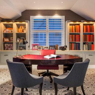 ロンドンの中サイズのトランジショナルスタイルのおしゃれなホームオフィス・書斎 (茶色い壁、カーペット敷き、自立型机、マルチカラーの床、ライブラリー、暖炉なし) の写真