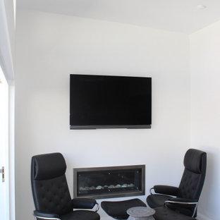 シドニーの大きいコンテンポラリースタイルのおしゃれなアトリエ・スタジオ (白い壁、ライムストーンの床、標準型暖炉、漆喰の暖炉まわり、造り付け机、グレーの床) の写真