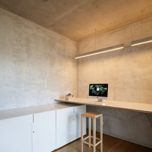 Mid-sized modern study room in Sydney with grey walls, bamboo floors, a built-in desk and beige floor.