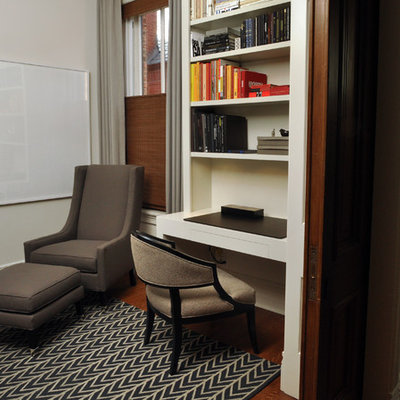 Inspiration for a mid-sized contemporary built-in desk medium tone wood floor study room remodel in Chicago with white walls