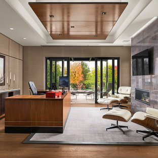 Exempel på ett stort modernt hemmabibliotek, med bruna väggar, mellanmörkt trägolv, en spiselkrans i trä, ett fristående skrivbord, brunt golv och en bred öppen spis