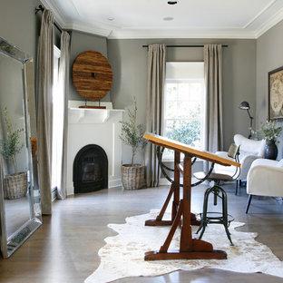Modelo de despacho clásico renovado, grande, con paredes grises, suelo de madera en tonos medios, chimenea de esquina, marco de chimenea de madera, escritorio independiente y suelo marrón