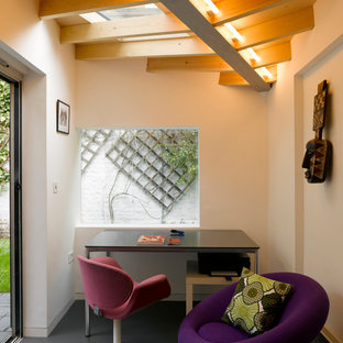 This is an example of a small contemporary study in London with white walls, a freestanding desk, black floors and no fireplace.