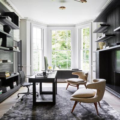 Large trendy freestanding desk light wood floor and beige floor study room photo in London