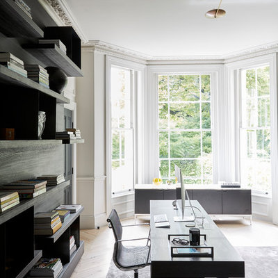 Example of a large trendy freestanding desk light wood floor study room design in London with white walls