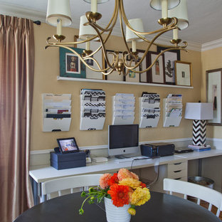 ロサンゼルスの中くらいのトラディショナルスタイルのおしゃれなホームオフィス・書斎 (黄色い壁、無垢フローリング、暖炉なし、造り付け机) の写真