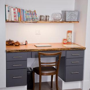 Cette photo montre un petit bureau craftsman avec un mur blanc, un sol en bois brun, un bureau intégré et aucune cheminée.