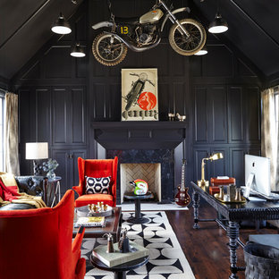 Inspiration for an eclectic study room in Nashville with black walls, dark hardwood floors, a standard fireplace, a stone fireplace surround and a freestanding desk.