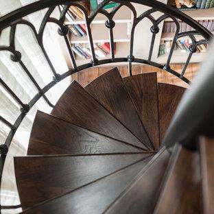 ヒューストンの大きいトラディショナルスタイルのおしゃれなホームオフィス・仕事部屋 (ライブラリー、ベージュの壁、濃色無垢フローリング、標準型暖炉、漆喰の暖炉まわり、茶色い床) の写真