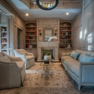 Foto di un grande studio classico con libreria, pareti beige, parquet scuro, camino classico, cornice del camino in intonaco e pavimento marrone