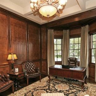 Großes Klassisches Arbeitszimmer mit Arbeitsplatz, brauner Wandfarbe, dunklem Holzboden, Kamin, Kaminsims aus Stein, freistehendem Schreibtisch und braunem Boden in Austin