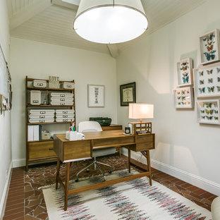 Modelo de despacho tradicional renovado con paredes blancas, suelo de baldosas de terracota, escritorio independiente y suelo marrón