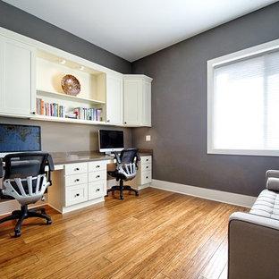 シアトルの中サイズのトランジショナルスタイルのおしゃれなホームオフィス・仕事部屋 (ライブラリー、青い壁、竹フローリング、暖炉なし、造り付け机、茶色い床) の写真